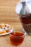 Teatime: taza de té, de tetera y de galletas Imágenes de archivo libres de regalías