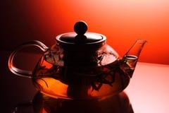 Teatime - tekanna med örtte, studioskott som tänds med apelsinen Arkivbild