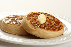 Teatime treat of crumpets and butter Stock Photos