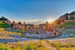 Teatro antiguo de Taormina con el Etna que entra en erupción el volcán en la puesta del sol Imágenes de archivo libres de regalías