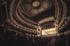 Teatro completamente dos povos que escutam a orquestra sinfônica Fotografia de Stock Royalty Free