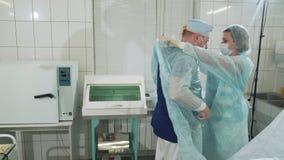 Teatro de funcionamento estéril O doutor está preparando-se para a cirurgia A enfermeira ajuda-o a calçar um vestido especial e l vídeos de arquivo
