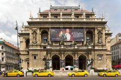 Teatro de la ópera de Budapest con los coches amarillos del taxi en frente Foto de archivo libre de regalías