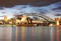 Teatro de la ópera de Sydney de la noche con el puente del puerto Foto de archivo libre de regalías