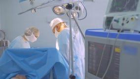 Teatro de operaciones Personal médico en el cuarto opearing que realiza cirugía almacen de metraje de vídeo