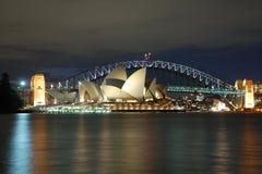 Teatro dell'Opera di Sydney di notte con il ponticello del porto Immagini Stock