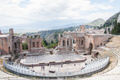Teatro di Taormina with Etna volcano in the background, Sicily, Italy. Ruins of the greek roman theater of Taormina, Sicily, Italy on a hot summer day Royalty Free Stock Image