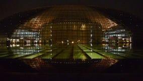 Teatro magnífico nacional de Pekín China en la reflexión en agua del lago en la noche de la tarde almacen de video