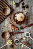 Tebjudninguppsättning Tekrukan, koppar, torkade teblad, fllowers, kryddor på bästa sikt för träbakgrund fotografering för bildbyråer