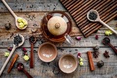 Tebjudninguppsättning Tekrukan, koppar, torkade teblad, fllowers, kryddor på bästa sikt för träbakgrund royaltyfri bild