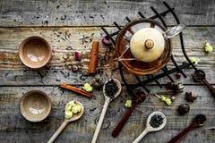 Tebjudninguppsättning Tekrukan, koppar, torkade teblad, fllowers, kryddor på bästa sikt för träbakgrund Arkivbild