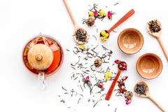 Tebjudninguppsättning Tekrukan, koppar, torkade teblad, fllowers, kryddor på bästa sikt för vit bakgrund arkivbilder