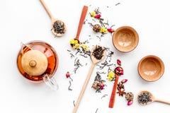 Tebjudninguppsättning Tekrukan, koppar, torkade teblad, fllowers, kryddor på bästa sikt för vit bakgrund Royaltyfria Bilder