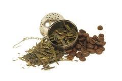 Teblad och kaffebönor med filtert Arkivfoto