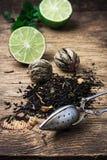 Tebrygd med limefrukt och mintkaramellen på träbakgrund royaltyfria foton