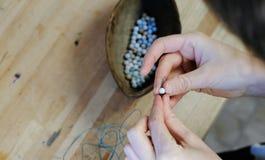 Tecelagem dos grânulos O close-up de um ` s da mulher entrega a amarração de grânulos na linha, fazendo a joia na oficina Vista t Imagens de Stock