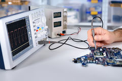 Tech fixes motherboard in service center. Shallow DOF, focus on hand, part of moherboard and front part of oscilloscope Royalty Free Stock Images