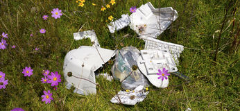 Tech garbage. Old computer disposal in a green field, broken old technology garbage contaminate a flowers field, trow it away personal computer stock photos