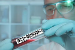 Tech with a medical sample. Labeled with a barcode stock photos