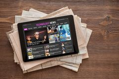 Tech news website on tablet on stack of newspapers. royalty free stock image