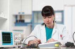 Tech repairs electronic device in modern lab Stock Photos