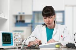 Tech reparerar den elektroniska apparaten i modern labb Arkivfoton