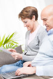 Tech savvy couple with a laptop and tablet Stock Photos