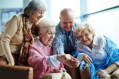 Tech-savvy seniors with smartphone. Four tech-savvy senior people gathered together and taking selfie with modern smartphone against panoramic window Royalty Free Stock Photography