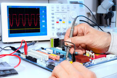Tech tests electronic equipment. In service centre Stock Images