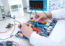 Tech tests electronic equipment. In service centre stock image