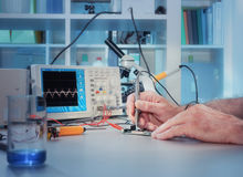 Tech tests electronic equipment. In service centre Royalty Free Stock Photography