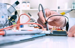 Tech tests electronic equipment Stock Photo