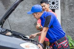 Techinician help customer fixing his car. In the house Stock Photo