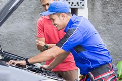Techinician help customer fixing his car. In the house Royalty Free Stock Photos