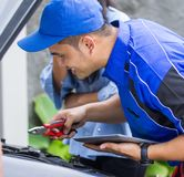 Techinician help customer fixing his car. In the house using tablet pc Royalty Free Stock Image
