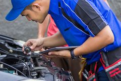 Techinician help customer fixing his car. In the house using tablet pc Royalty Free Stock Images
