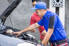 Techinician help customer fixing his car. In the house Stock Images
