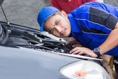 Techinician help customer fixing his car. In the house Stock Photos