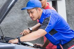 Techinician help customer fixing his car. In the house Stock Photography