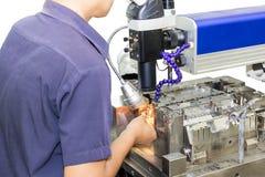 Techncian pendant le moule métallique de réparation et mourir partie par la méthode de soudure laser sur le fond de wihte photographie stock