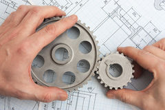 Technical drawing. And pinion gears in hands stock photo