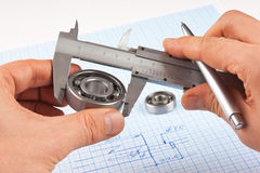 Technical drawing and callipers with bearing in hand Stock Photos