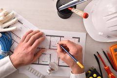 Technical engineer in electricity writing in an electrical plan top stock photography