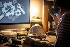 Technical engineer feeling stressed while repairing drone. Asian technical engineer feeling stressed while repairing drone with computer and other tools on desk Stock Image