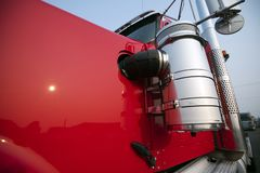 Part of red big rig semi truck tractor cab with chrome accessoriae. The technical equipment of big rig semi trucks are given great importance since trucks are stock image