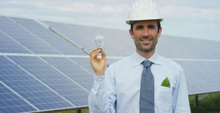 Technical expert in solar energy photovoltaic panels, remote control performs routine actions for system monitoring using clean, r Stock Photos