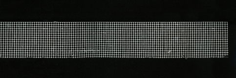 Technical fabric - paint the grid with square cells. Texture technical mesh to reinforce the gluing and puttying the joints of panels and slabs of drywall. used Royalty Free Stock Photo