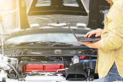 Technical man is using laptop to tuning racing car with engine bay royalty free stock photography