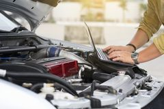 Technical man is using laptop to tuning racing car with engine bay stock image
