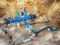 Technical open gate valve on drink water pipes joined with new black waga multi joint members into old pipeline system. Stock Photos